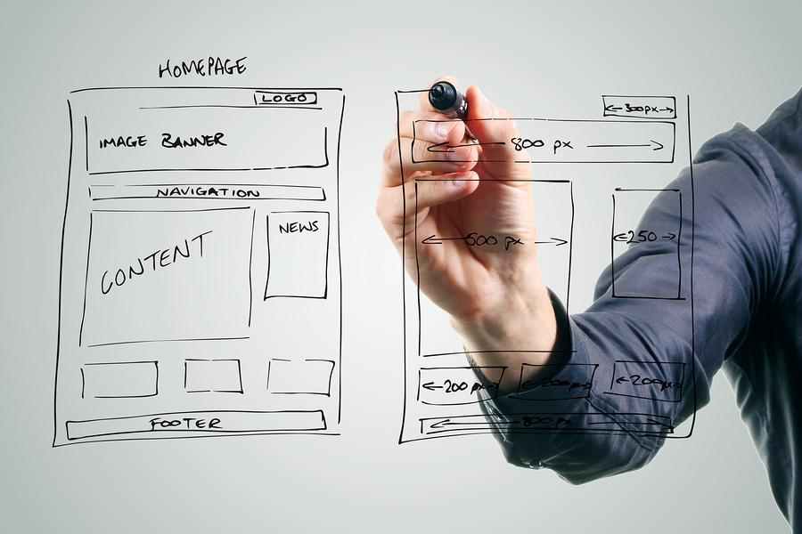designer drawing website development wireframe with black marker